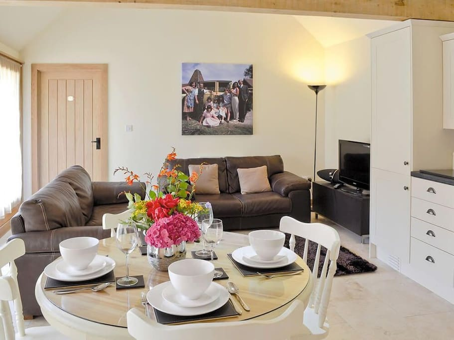 Sitting & dining areas in the open plan living space with wooden beamed vaulted ceiling