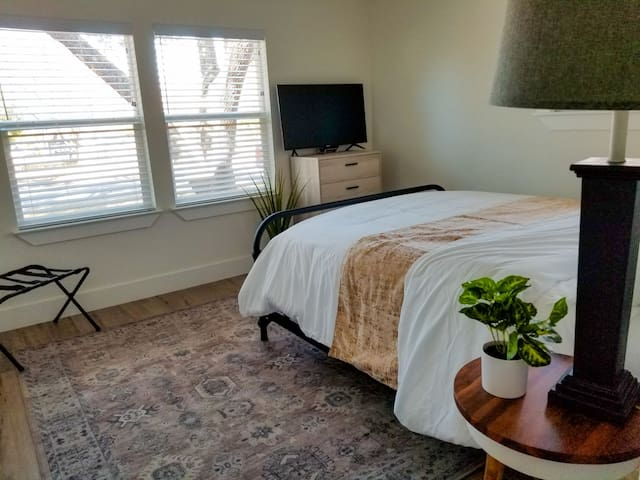 """Queen sized bedroom with dresser and 40"""" tv"""