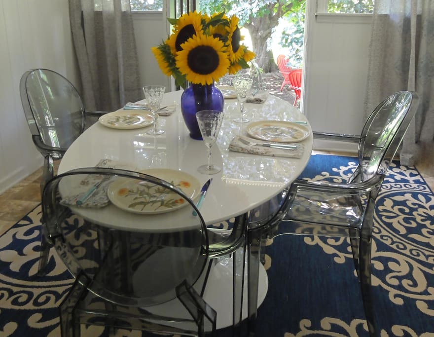 A dining room seating 6 with ghost chairs and a tulip pedestal table