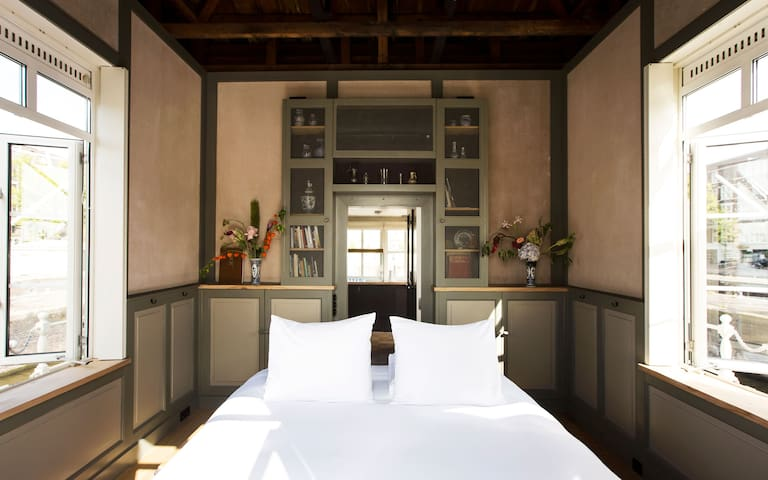 The bright bedroom has windows on three sides. Its interior was inspired by the 17th century.