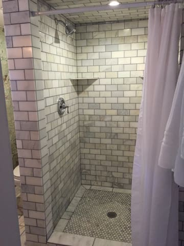 Our full marble bath is a short walk from the treehouse and features a luxurious marble walk-in shower.