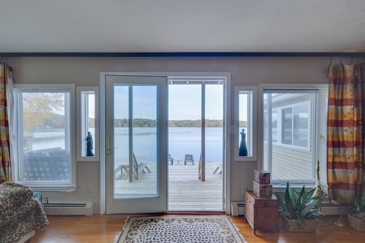 Looking out the full size French glass door out to the wooden two tiered deck viewing Billington Sea
