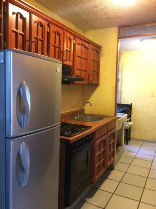 Cocina Integral con refrigerador, horno de microondas, vajilla, cubiertos y accesorios para cocinar.