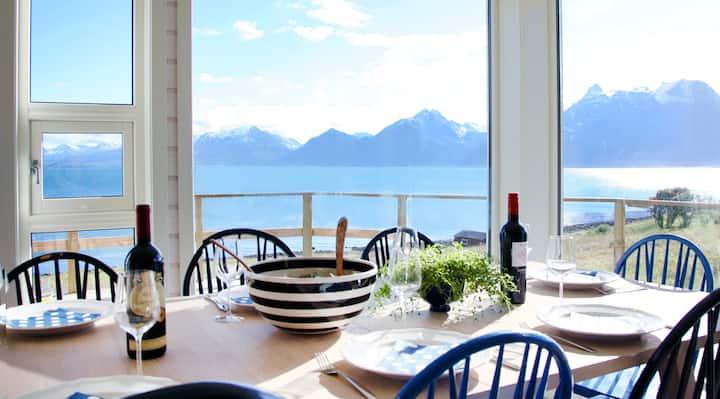 Moderne hytte ved strand, utsikt til fjell & fjord