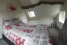Beamed master bedroom with field views, king size bed, wardrobe & drawers.
