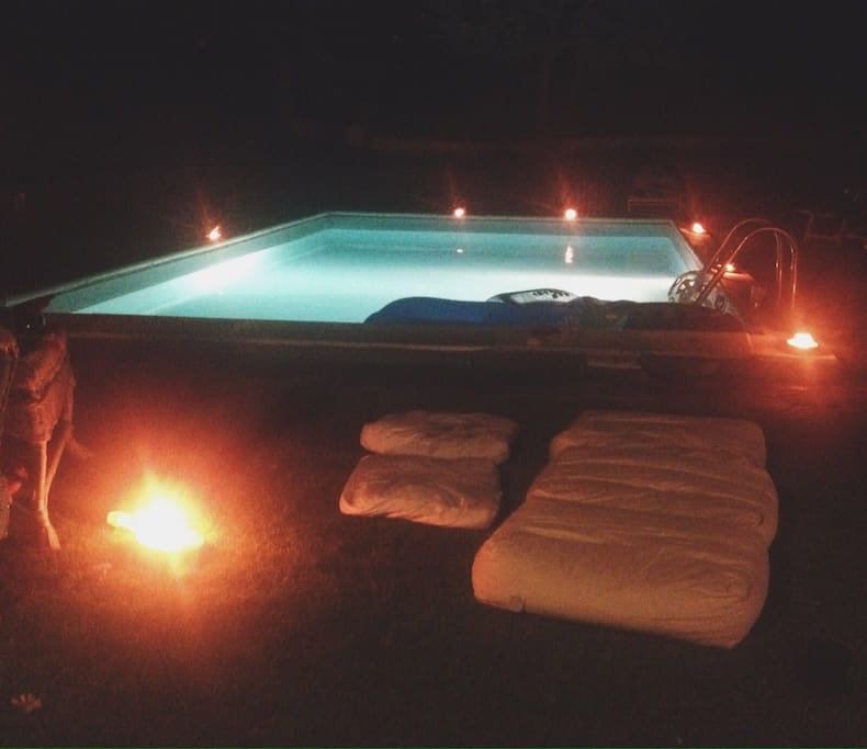 Swimming pool at night with candles on the side