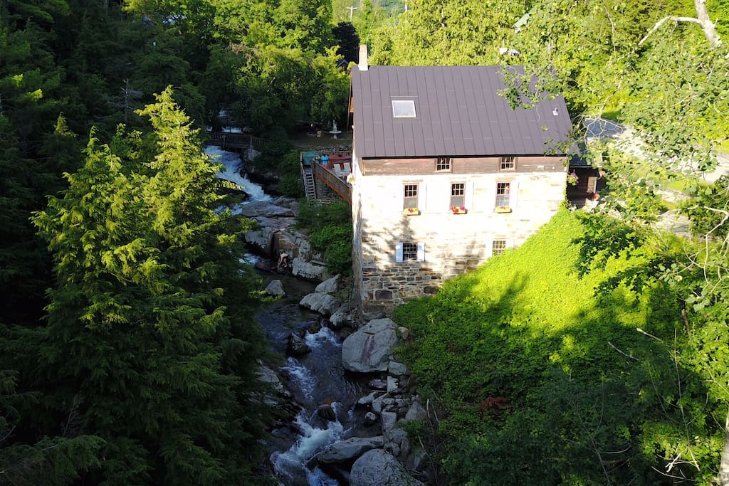 """Aerial view looking upstream at the Millhouse, the footbridge and the campsite """"Cozy Screen House on a Waterfall""""."""