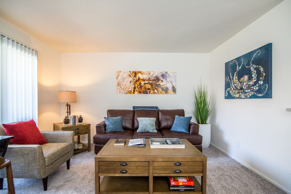 Living room with modern glass artwork, sleeper sofa, and coffee table equipped with coasters, board games, extra throw pillows, and books for casual reading
