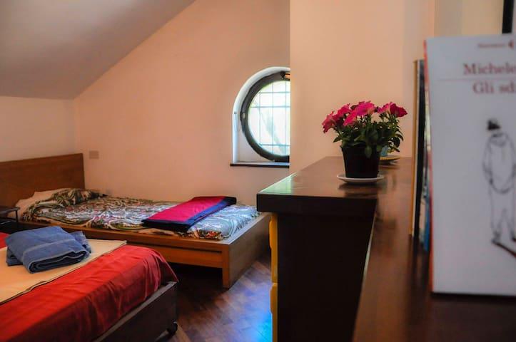 Camera da letto per due persone composta da letto alla francese e letto singolo, armadio a muro e cassettiera.