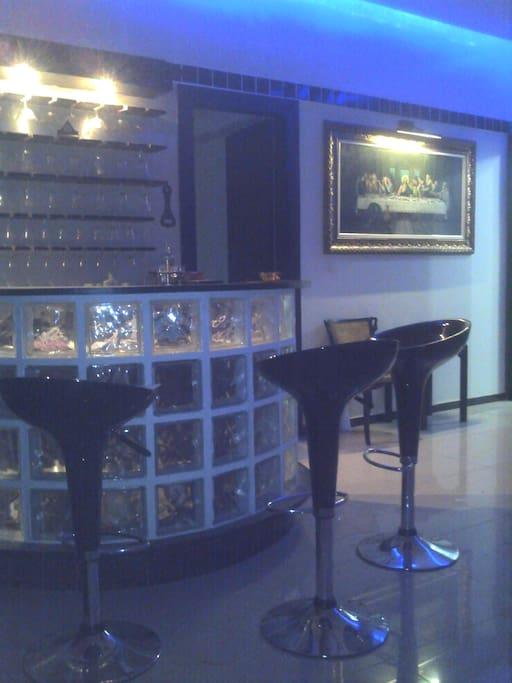 Bar em tijolos de vidro anexo a sala