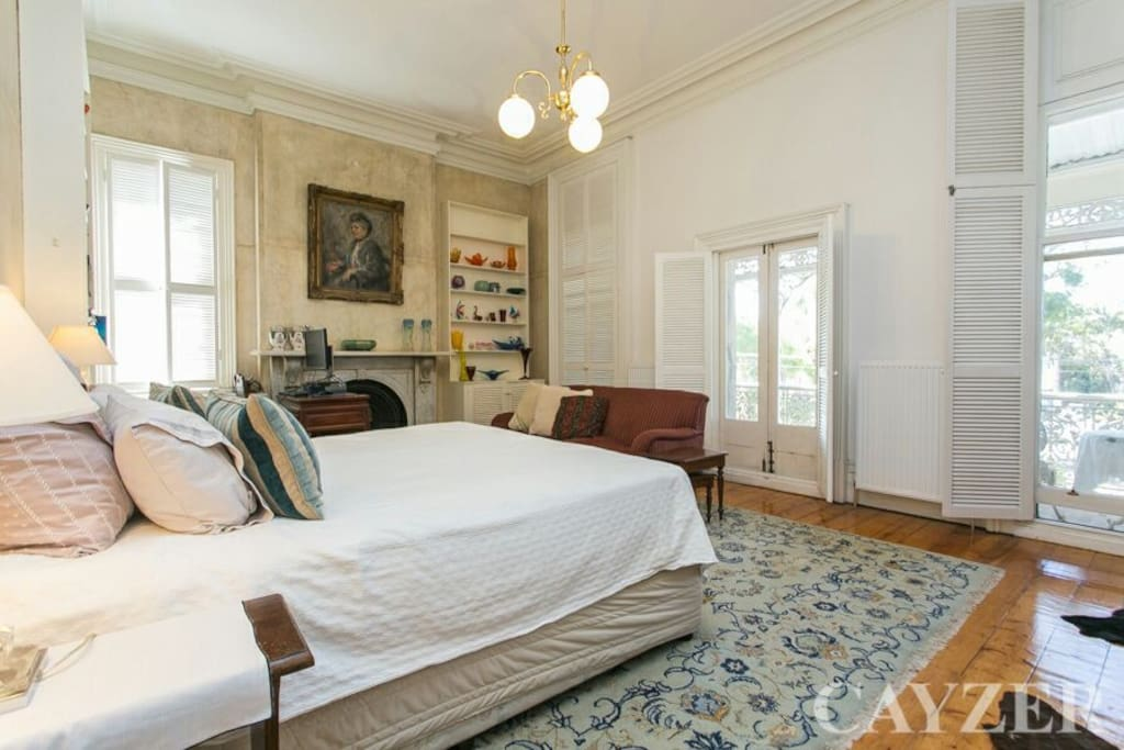 This is the large main bedroom with a King bed and a balcony overlooking a park.TV heating and a marble fireplace with a quality Madison bed