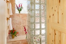 The second floor shower features glass blocks and marble with a view from the shower, of course. The natural pine door on the right leads to a stacked washer and dryer.