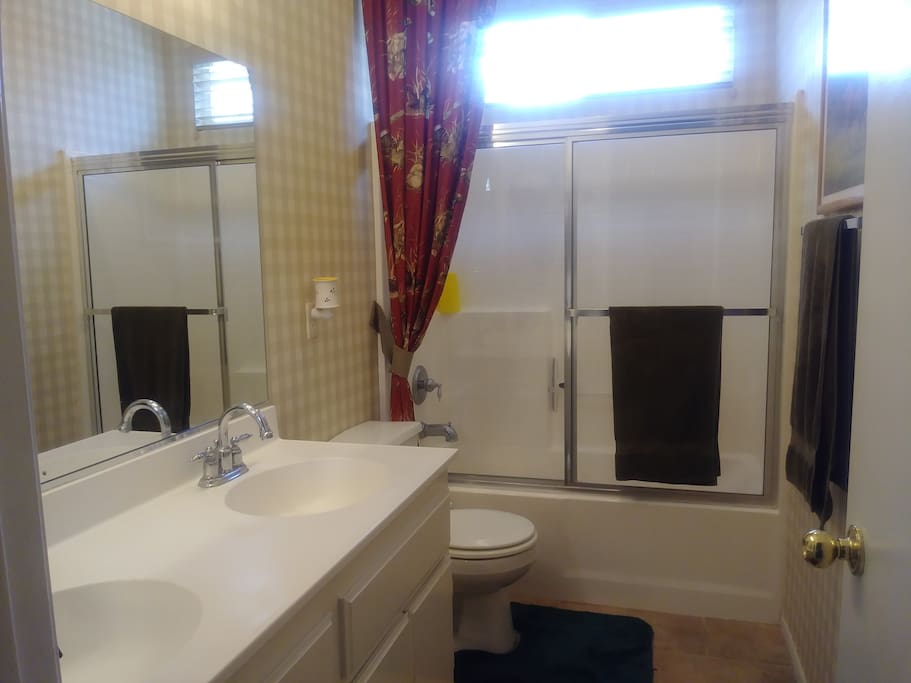 Clean bathroom with tub-shower combo, and dual sink vanity