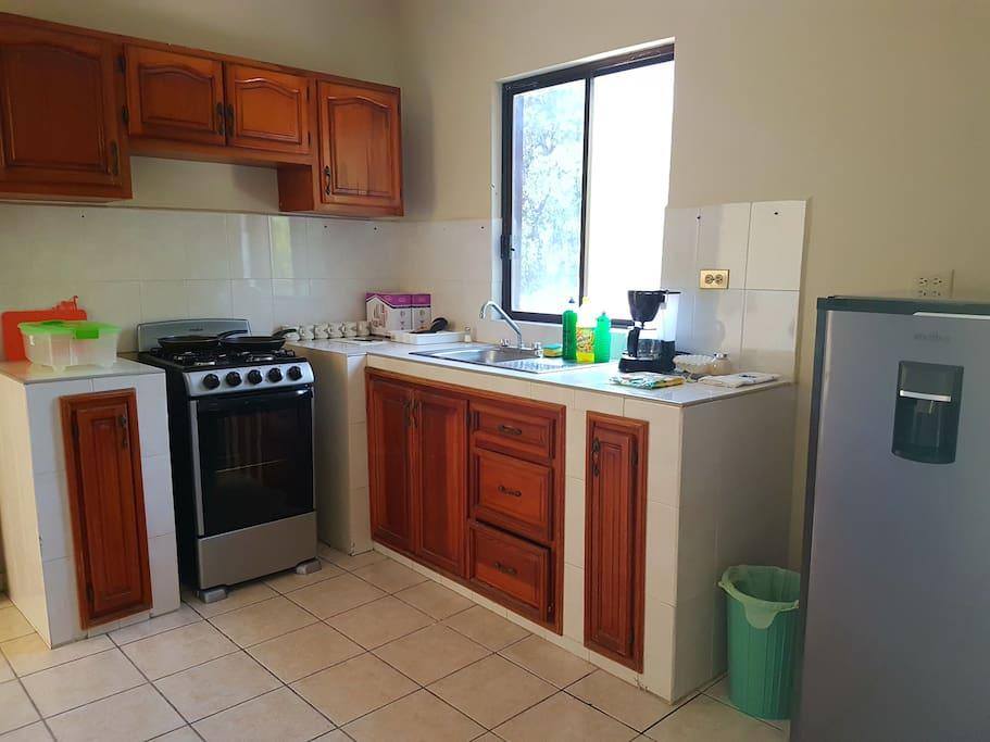 Cocina con estufa, refrigerados, cubiertos, platos, cafetera, etc.