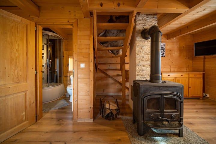 Domek z drewnianych bali ogrzewany kominkiem