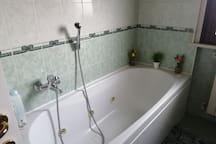 Vasca idromassaggio nel bagno con finestra e vista panoramica a 180 gradi sulla catena montuosa della Bella Addormentata
