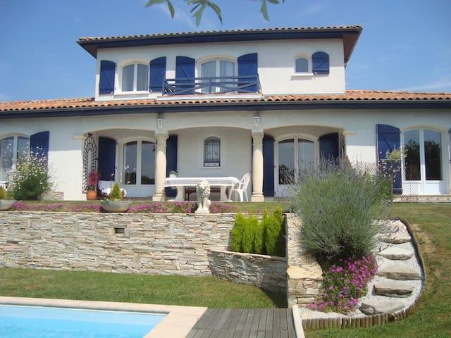 Vue d'ensemble de la maison, avec la piscine et la terrasse.