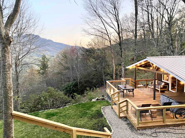 A cozy cabin nestled in the hillside with an expansive back deck so that you can take in the view of Grandfather Mountain from the outdoor sofa, enjoy dinner outside, or relax in the hot tub under the dimmable string lights.