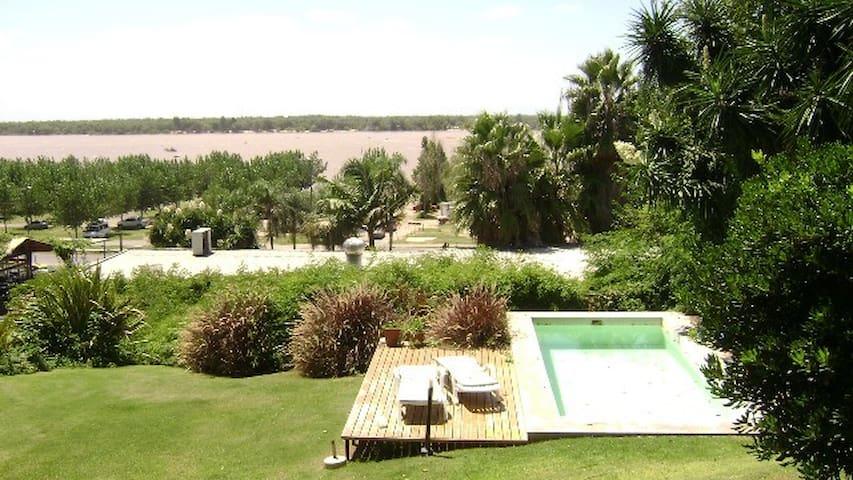 >Casa con piscina frente al río a mts de la playa