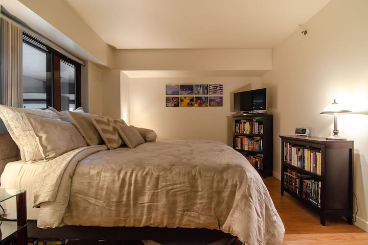 Enjoy one of the largest apartment bedrooms in the city. Fitting a whole king bed with lots of space to walk around. Take a moment to check out one of more than 1000 books from the library, to sit and enjoy in comfort.