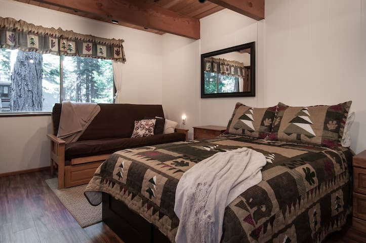 Pine Cone has 3 bedrooms. The downstairs bedroom sleeps up to 4 folks. It has a double and a double futon, and oh yes, more trees out the window.