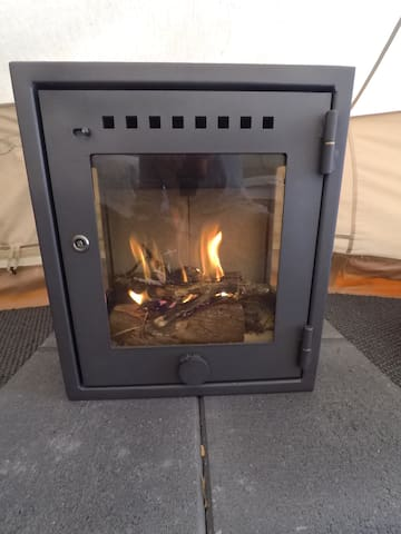 Our specialist glamping wood burning stove INSIDE the tent. Made for a bell tent. Perfect for those chilly winter nights. Snuggle up in bed and watch the fire together.