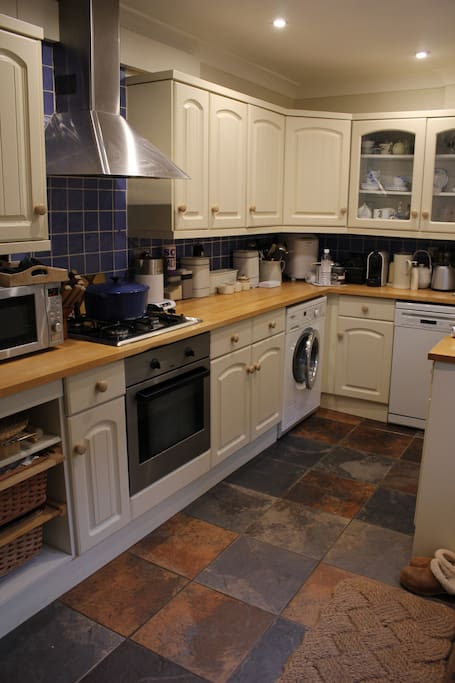 A well equipped kitchen with miele dishwasher and washing machine and a large belfast sink.