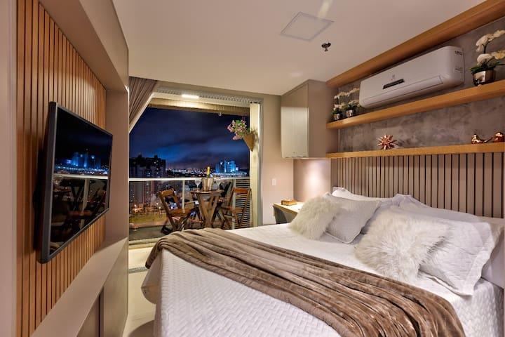 Quarto com cama de casal, painel de TV giratório, varanda e espaço para trabalho/estudos.