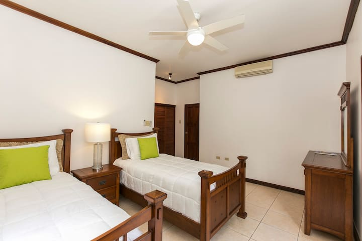 2nd bedroom -Great for children or young adults.  This bedroom faces the hills is actually the coolest bedroom in the villa ensuite bathroom. Air-condition and ceiling fan. The presentation of the beds changes seasonally.
