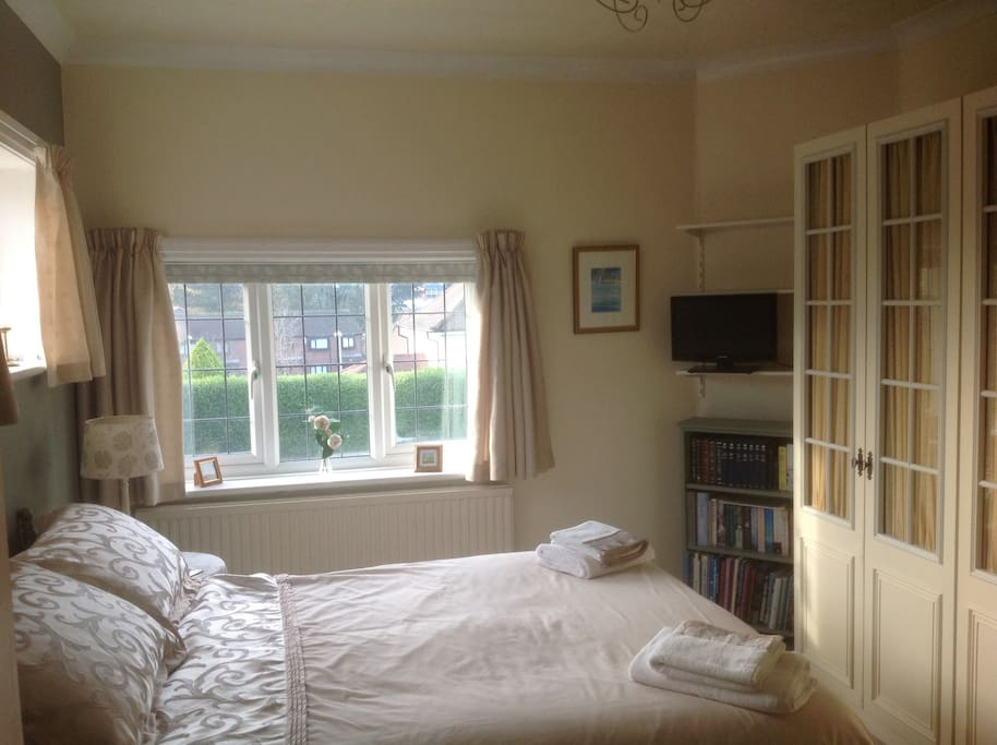 Sunny  double bedroom with tv and wardrobes.
