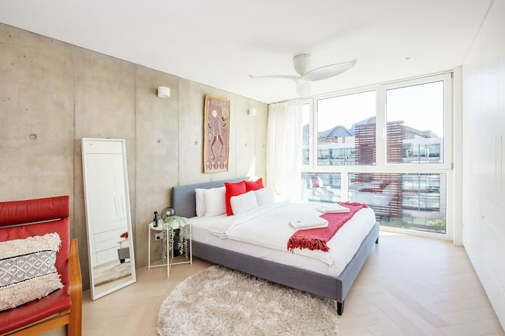 The bedroom features a king bed, ample built-in storage space, and shut-out blinds. With triple-glazed doors and windows throughout, enjoy a good night's sleep in complete peace and quiet.