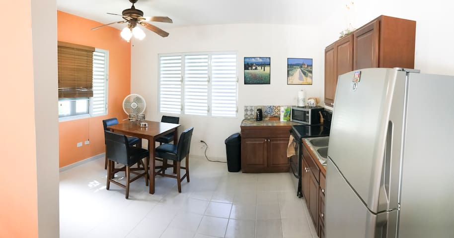 Fully equipped kitchen with full-size electric stove and refrigerator.