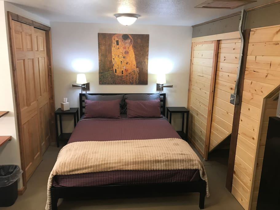 A comfortable queen bed with reading lamps and  nightstands. A closet offers storage for clothes and other small items.