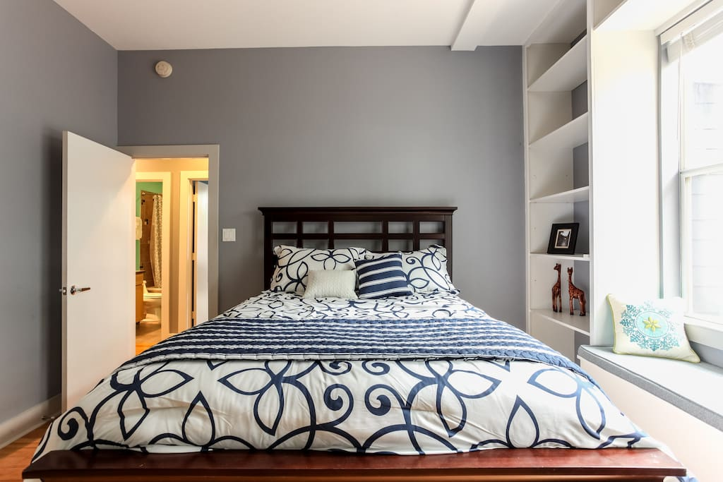 2nd bedroom, queen bed with lots of shelving and a window seat