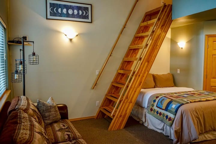 """View of the """"stairs"""" to the loft and first floor queen size bed. **The ladder is the only way into the loft**"""