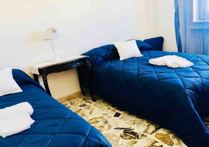 Camera da letto con un letto da una piazza e mezza ed uno matrimoniale
