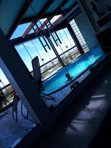 Casa com vista para o mar e piscina interna.