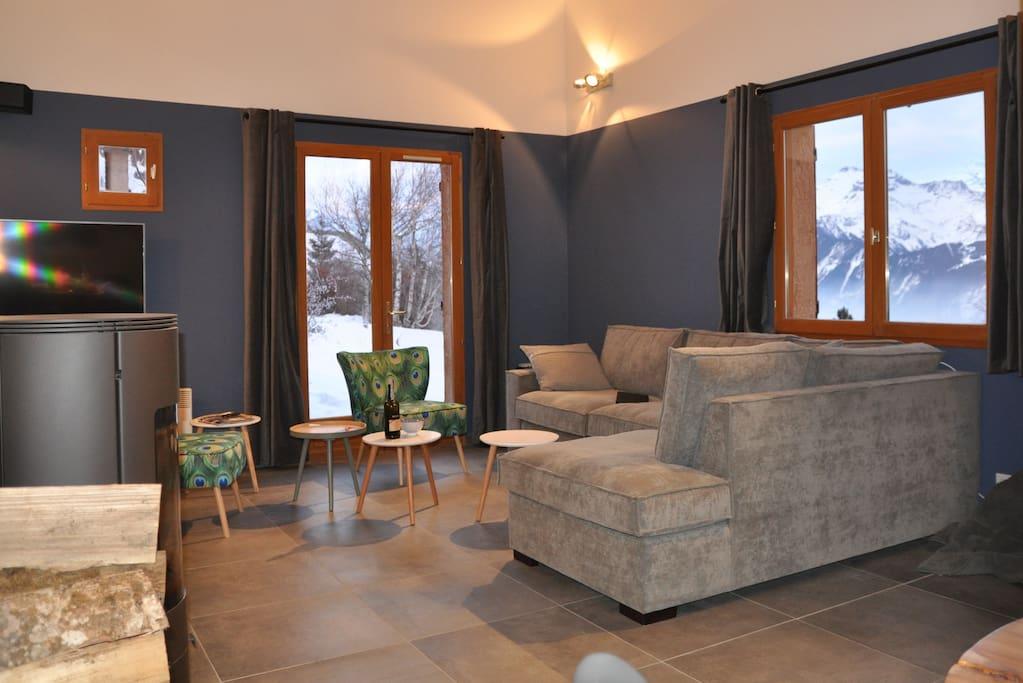 De woonkamer met comfortabele hoekbank, gezellige houtkachel en TV met Netflix en AirPlay