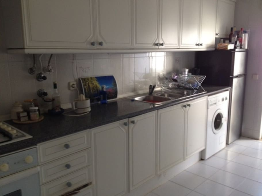 Fully equipped kitchen with sliding doors leading to a balcony