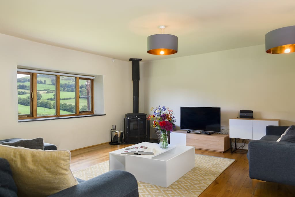 Main lounge with log burner and two comfy sofas. SmartTV with Netflix, books and games.