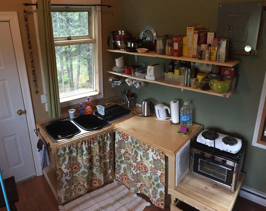 Kitchenette with mini fridge, kettle, hot plate, toaster oven, coffee and tea, and cooking supplies.