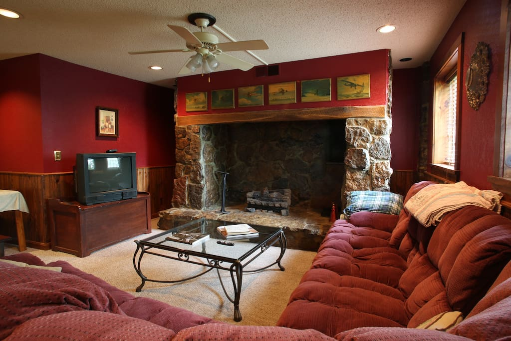 Spacious living room with huge fireplace.  Behind the couch is the pool table and fussball table. Extra pillows and blankets provided here as well.
