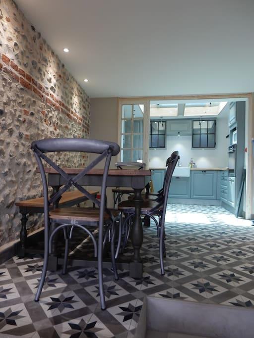 Magnifique mur moitié briques et galets découvert lors de la rénovation.   Table fait de la main d'un ébéniste pour accompagner vos soirées en Famille sous le signe de la convivialité. Espace ouvert sur la baie.