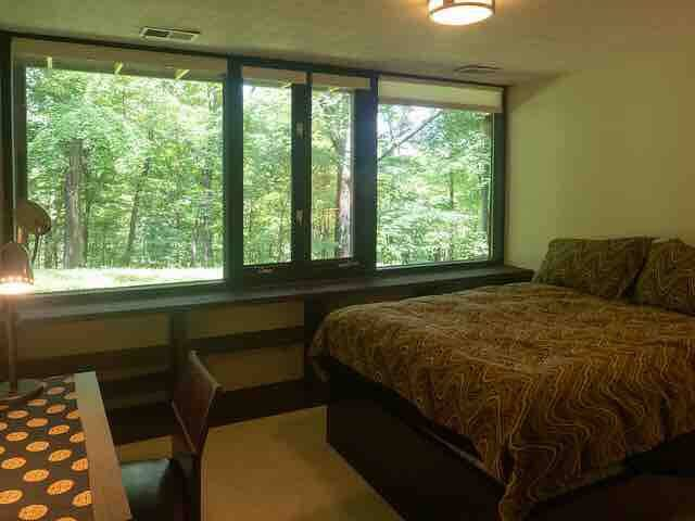 Full-size bed in lower level guestroom has cotton sheets, pillowcases and poly fill duvet. There is a large empty closet in this room with blankets available. Small study desk opposite the bed.