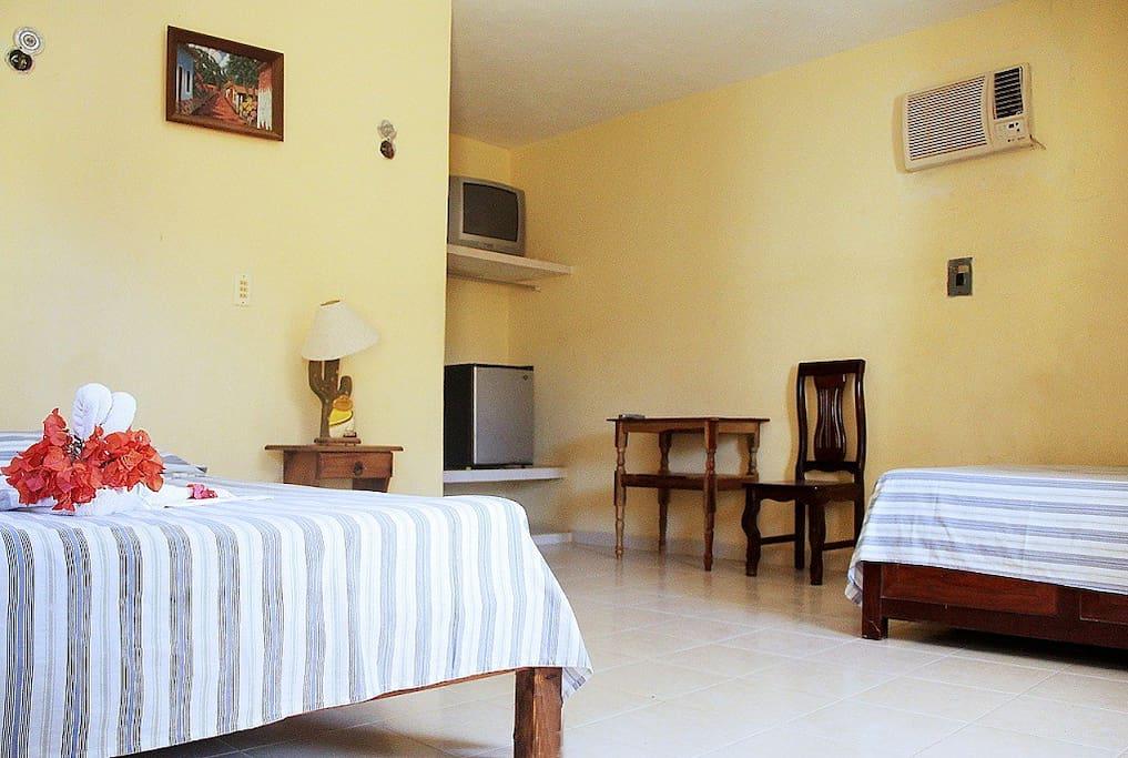 Habitación equipada con TV, Aire acondicionado, frigobar, dos camas matrimoniales