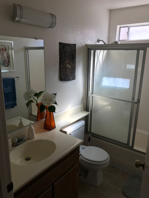 A bathroom all to yourself with shower/bathtub, clean towels, shampoo, body wash, and hair dryer.
