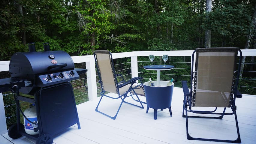 View of the smoker grill, glider chairs and table with built in cooler!