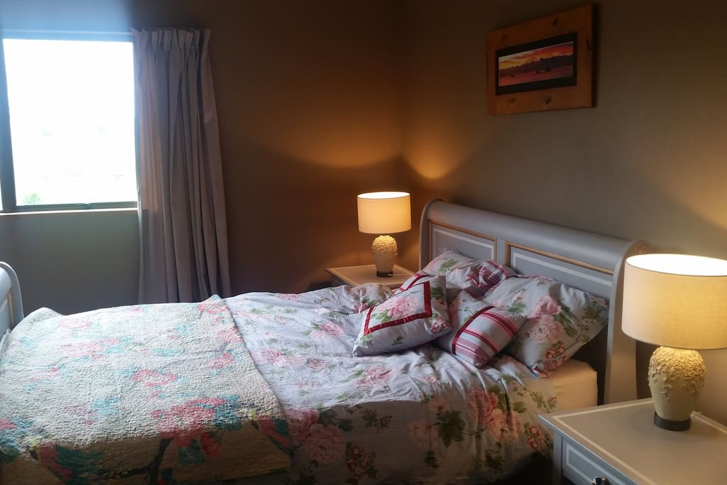 cozy room furtished with reading lamps a queen bed with a solid latex mattress and memory foam topper.