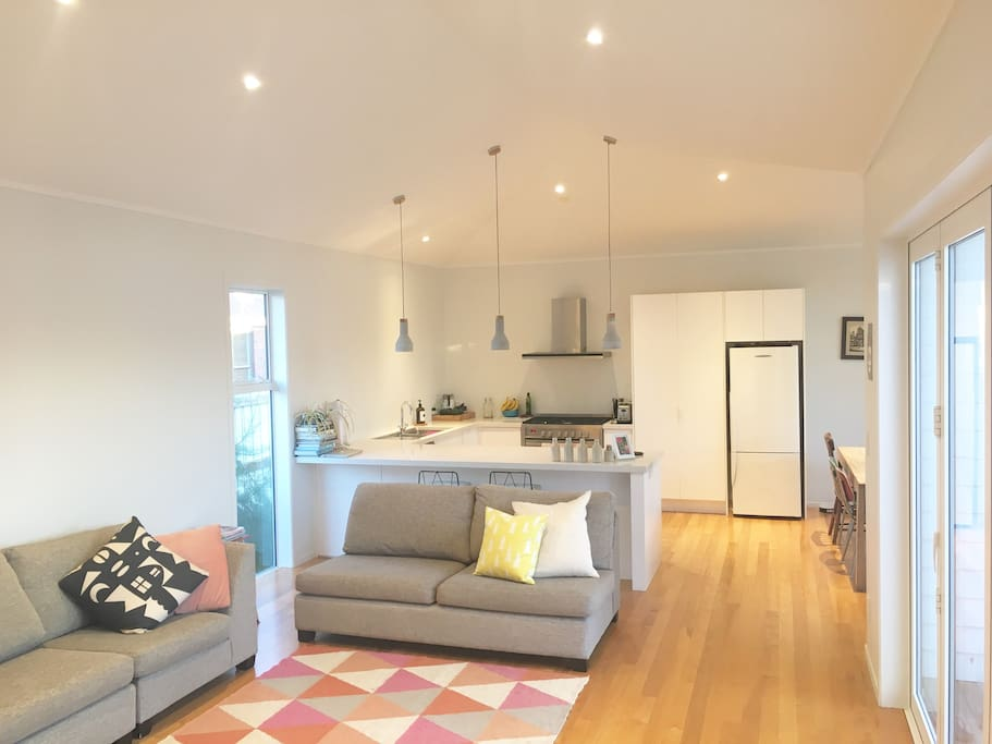 Light, airy open plan lounge, dining and kitchen includes a cosy wood fire and opens to a large deck.