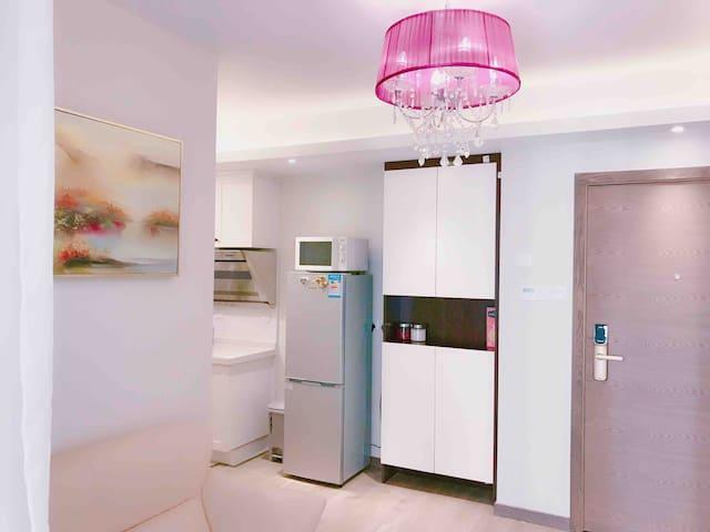 开门后,右边鞋柜,换上拖鞋,舒服呢。3人沙发,时尚的桔粉色,紫色水晶吊灯,漂亮啊。同色系的地毯和白色小茶几